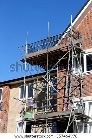 Scaffolding on exterior of modern building with blue sky background.