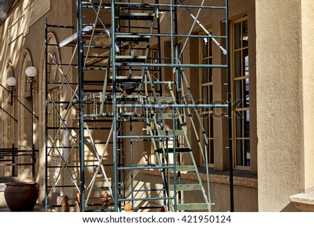 Scaffolding set up on building for renovations, repair and painting showing windows and architecture