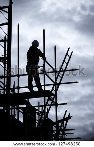 scaffolding silhouette of construction worker, Blue toned - stock photo