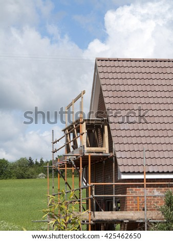 Scaffolding to the side of a new build residential house - stock photo