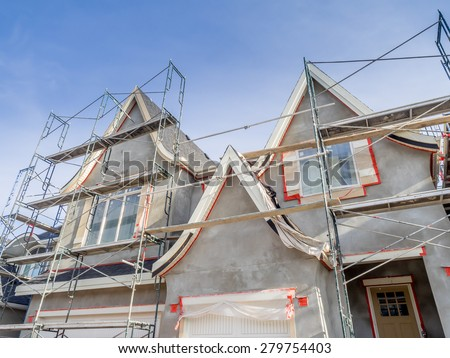 Scaffolds surrounding home following application of smooth exterior stucco but prior to painting. Home located in Calgary.