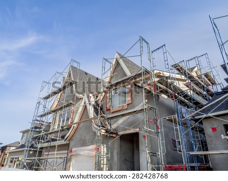 Scaffolds surrounding home following application of smooth exterior stucco but prior to painting. Home located in Calgary.  - stock photo