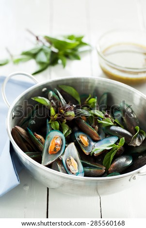 scald mussel in stainless steel pot with spicy seafood sauce
