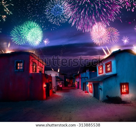 scale model of a mexican town at twlight with fireworks - stock photo