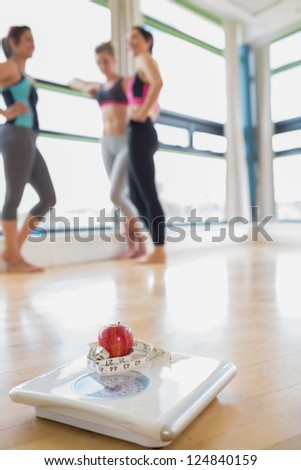 Scale with apple and measuring tape on floor of fitness studio