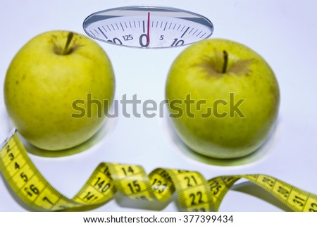 Scale with tape measure and apples