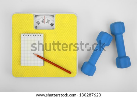 Scales, a notebook with a pencil and a dumbbell. Sports Concept - stock photo