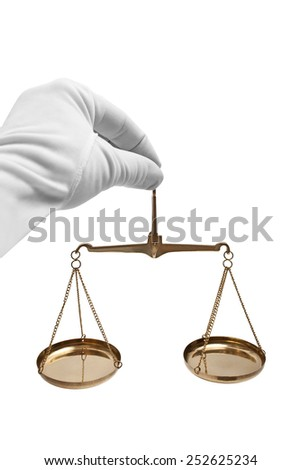 Scales of justice in his hand in a white glove. - stock photo
