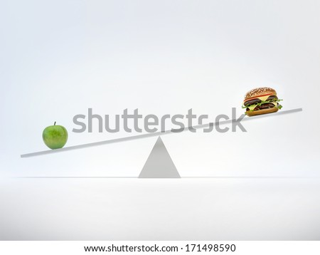 Scales with an apple and a hamburger. Concept healthy eating decision - stock photo