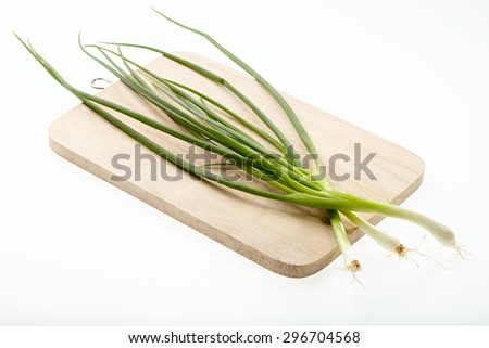 Scallion on chopping block isolated on white background. - stock photo