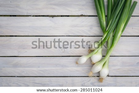 Scallions on a bright wooden table - stock photo