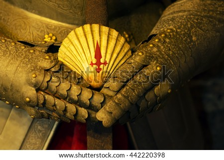 scallop pilgrim sign on  the sword hilt in medieval armour ; way of st james , camino de Santiago, Compostela, Spain ; selective focus - stock photo