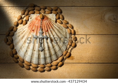 Scallop seashell and rosary beads with a silver crucifix on a wooden background. Symbols of Christian pilgrimage - stock photo