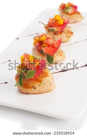 Scallop soaked with fresh yellow mango salsa, on white. - stock photo