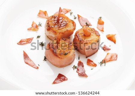 Scallops fried in bacon on plate, close-up shot - stock photo