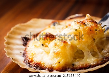 Scallops gratin on the wooden background