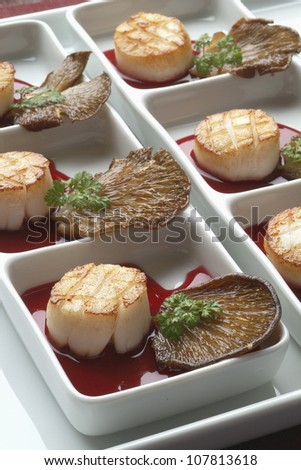 Scallops in wine sauce with fried pleurotus mushrooms - stock photo