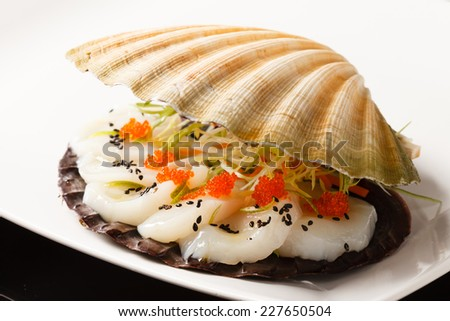 scallops presented on a scallop shell - stock photo