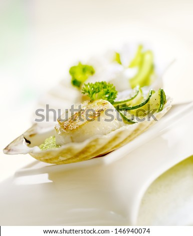scallops served in a scallop shell with zucchini - stock photo