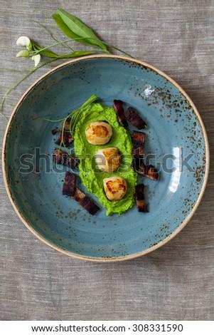 Scallops with pea puree and crispy bacon - stock photo