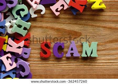 SCAM - words  made from multicolored   letters on wooden  background