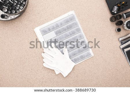 Scan and Archive Photos. Contacts, Cotton Gloves and roll of films on the Wooden Desk  - stock photo