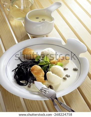 Scandinavian Codfish Dumplings with Squid Ink Pasta and Caper Sauce - stock photo