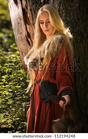 Scandinavian girl with runic signs holding a fur skins - stock photo