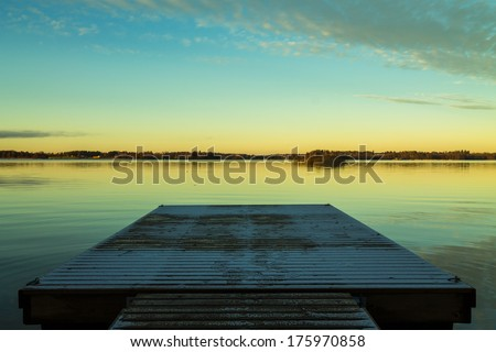 Scandinavian lake in the sunset with a frozen  jetty