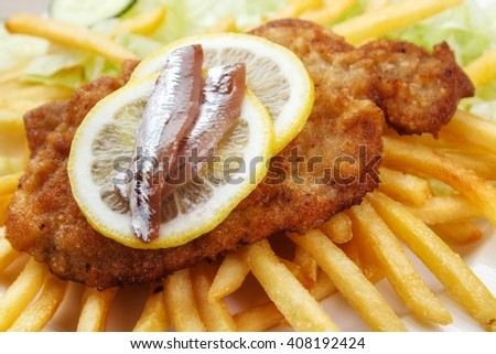 Scandinavian style wiener schnitzel closeup , served with lemon slices and anchovies , with french fries - stock photo