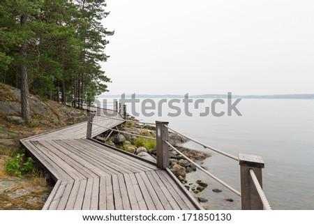 Scandinavian summer. Rocky lakeshore with wooden pathway. - stock photo