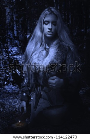 Scandinavian witch pythoness cooking potion in a dark forest - stock photo