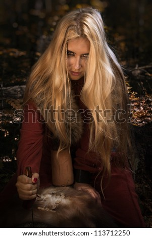 Scandinavian witch pythoness with runes on a forest background - stock photo