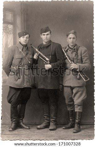 Scaned photo from WWII with three armed partisans in uniforms. - stock photo