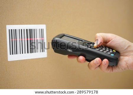 Scanning label on the box with barcode scanner - stock photo