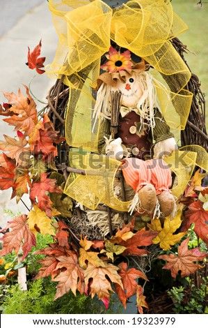 Scarecrow in a wreath wrapped with holiday ribbons and graced with fall leaves. - stock photo