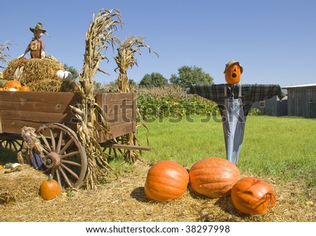 Scarecrows on a pumpkin farm with a wagon of hay, fall decorations, blue sky, horizontal with copy space - stock photo