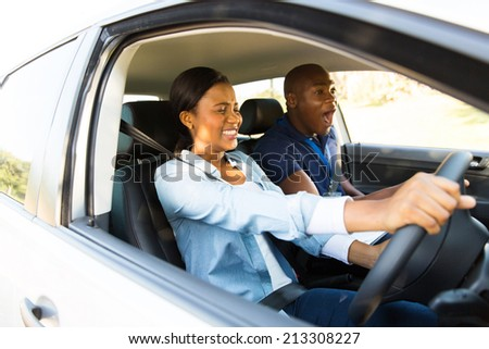 scared african girl taking driving lessons for the first time