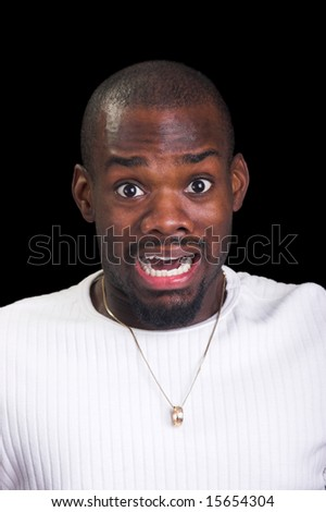 Scared Afro-American man against a black background - stock photo