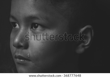 scared and alone and crying, young  Asian child who is at high risk of being bullied, trafficked and abused