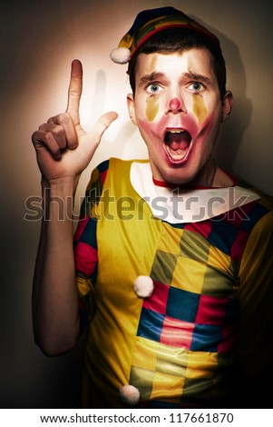 Scared And Frightened Clown Performer Gesturing A Hand Gun While Acting Out A Bank Heist During A Comedy Play Performance - stock photo
