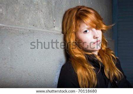 Scared and lonely, moody portrait of a beautiful fashionable young redhead girl.