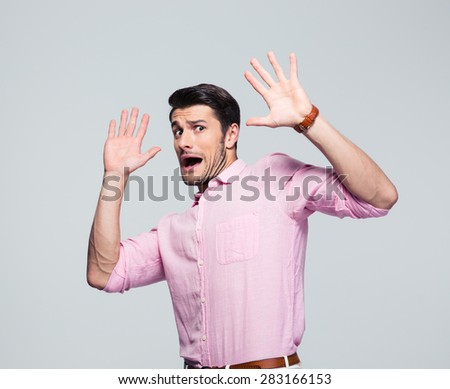 Scared and screaming businessman stop gesturing over gray background. Looking at camera