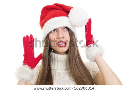 Scared and surprised teenage girl wearing Santa costume looking up
