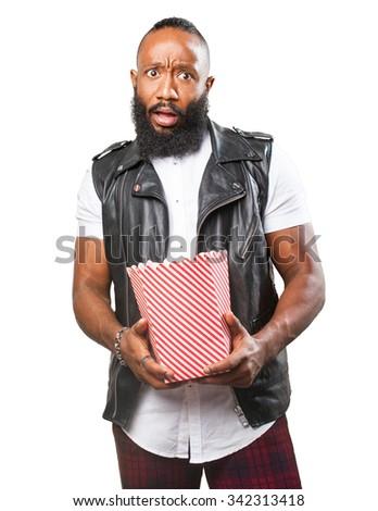 scared black man eating popcorn - stock photo