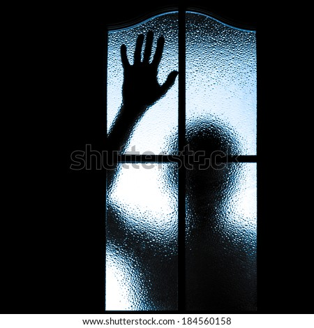 Scared boy behind glass door showing one hand - stock photo