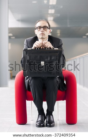 Scared Business Man Holding a Briefcase and Sitting on Red Armchair - stock photo