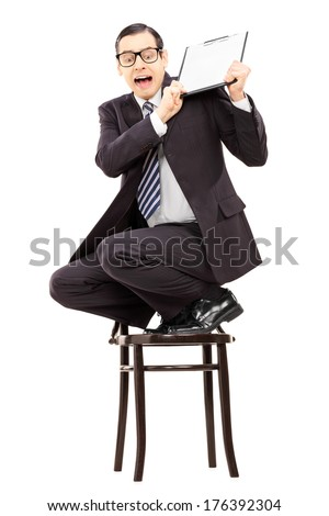 Scared businessman climbed on chair and swinging with clipboard isolated on white background - stock photo
