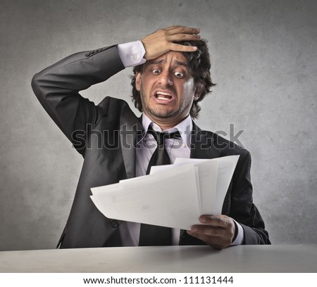 Scared businessman observing some bills - stock photo