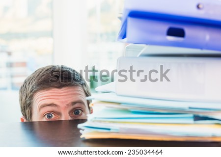 Scared businessman peeking over desk in his office